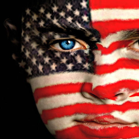Portrait of a young American football / soccer fan, with the American Flag on his face.